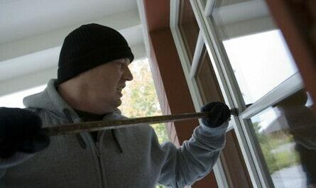 Einbrecher mit Brechstange am Fenster