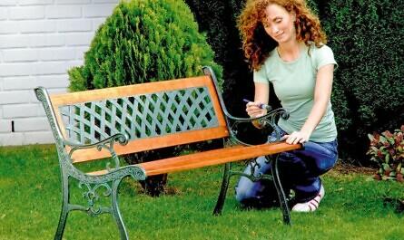 Frau streicht eine Bank im Garten