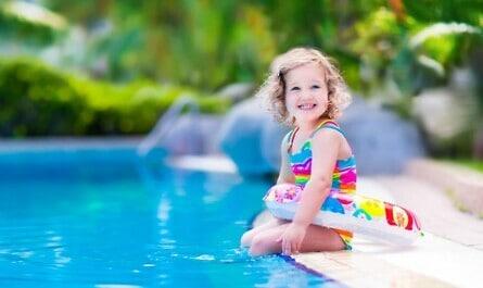 Mädchen sitzt am Pool