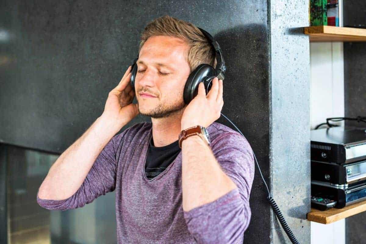 Mann mit Kopfhörer an Betonwand