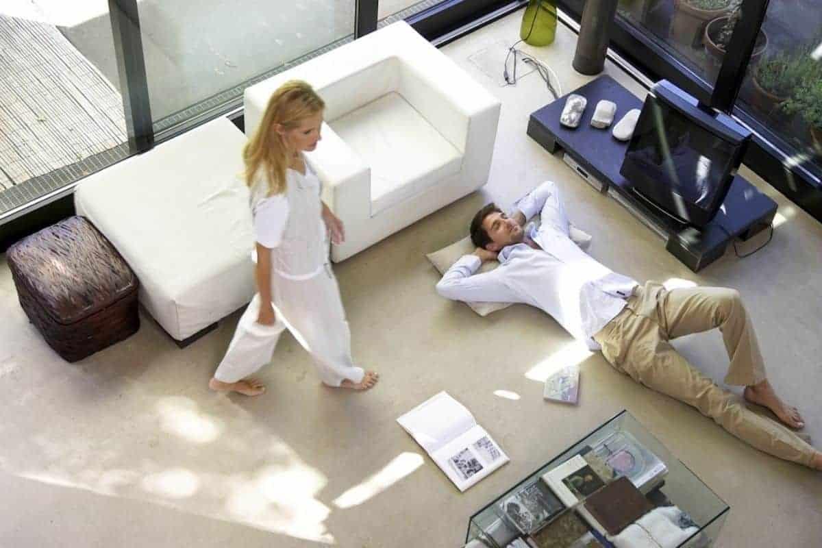Paar im Wohnzimmer mit Glasfassade