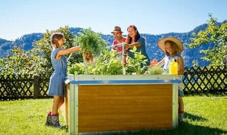 Familie pflegt Hochbeet im Garten