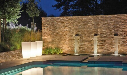 Leuchtende Pflanzgefäße am Pool am Abend