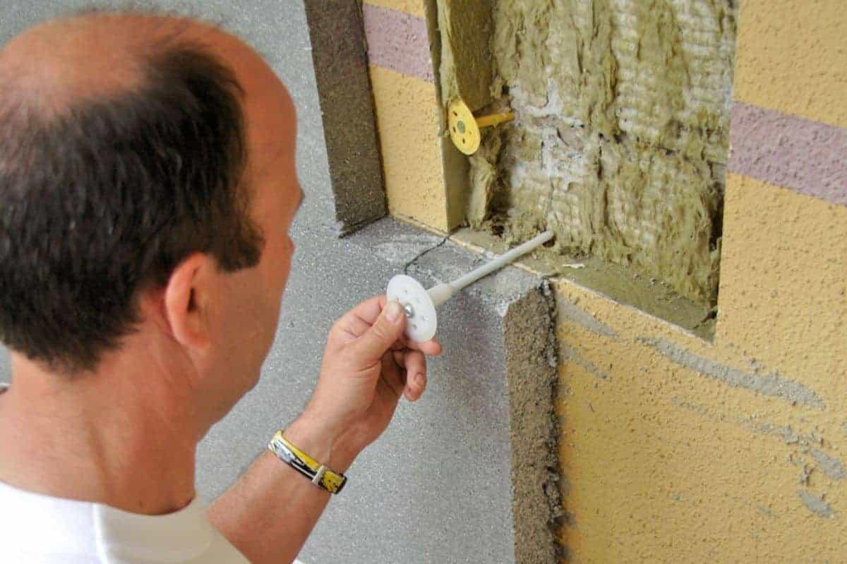 Mann dämmt Fassade