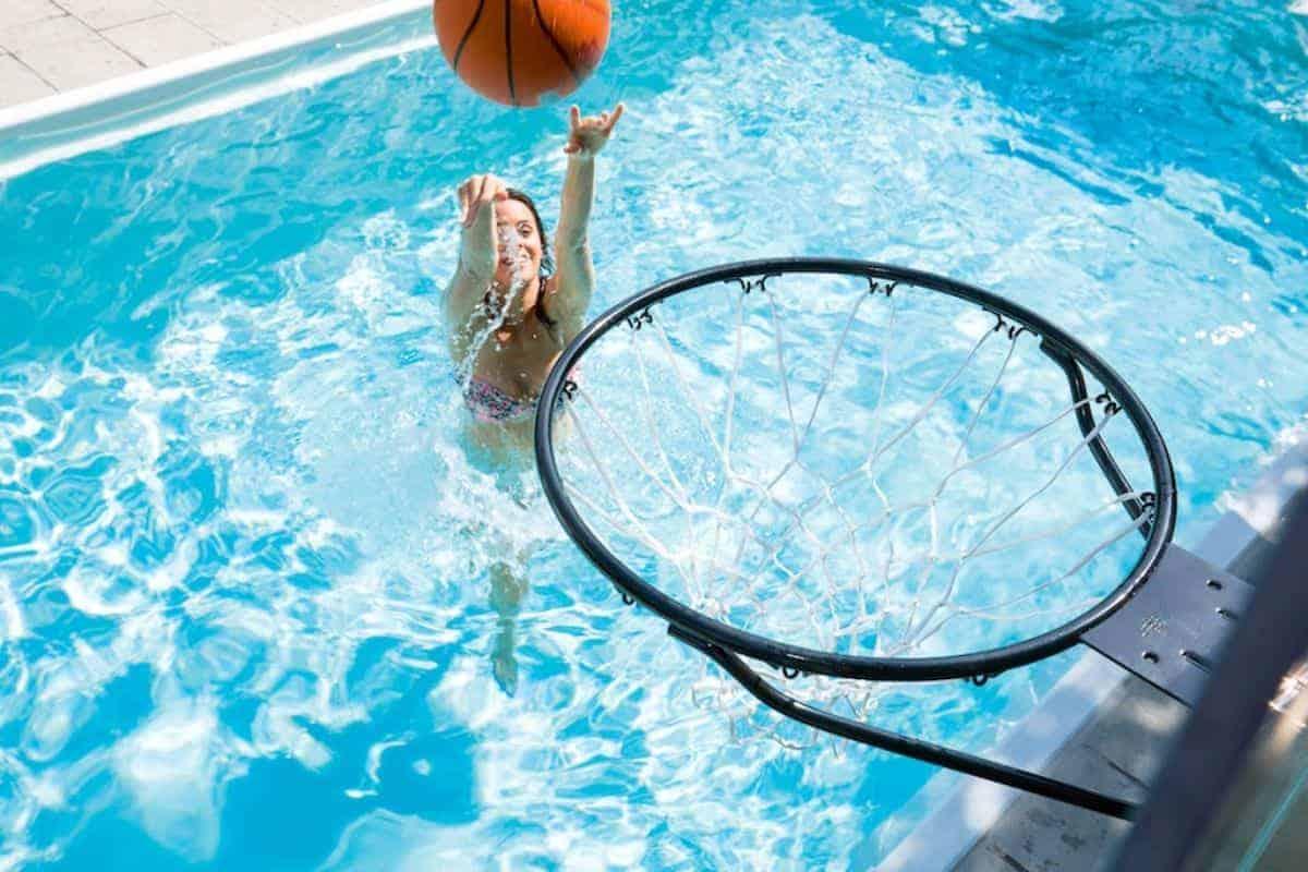 Frau spielt im Pool Basketball