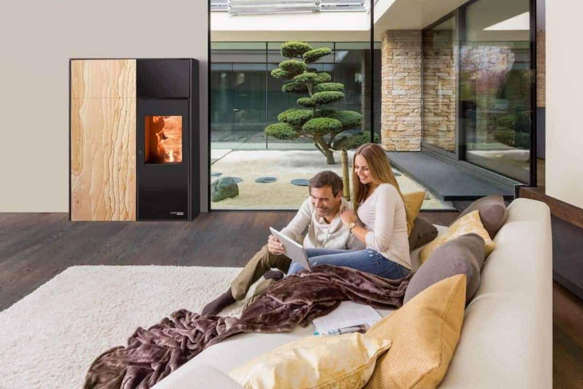 Paar auf Couch vor Kaminofen
