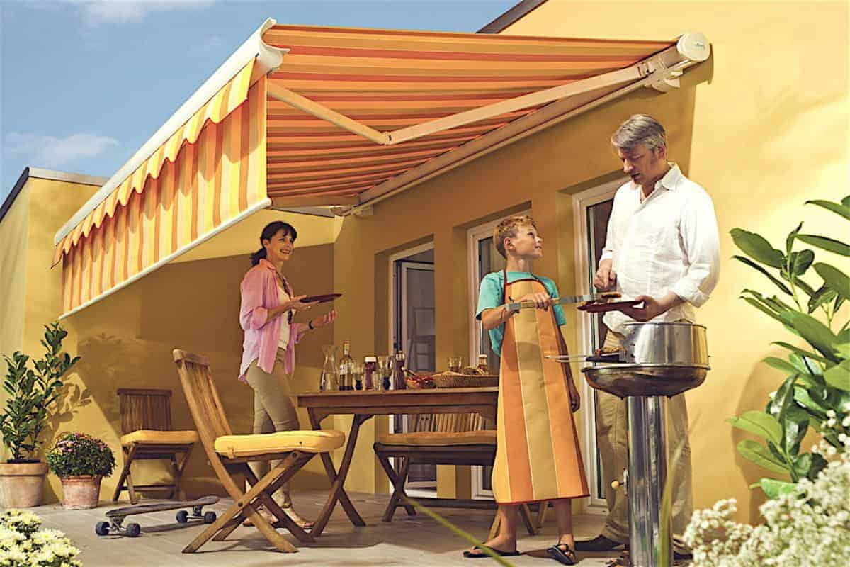 Familie grillt auf Terrasse mit Markisen
