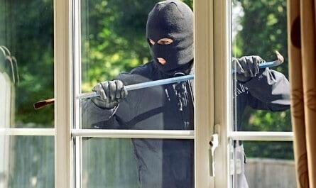 Einbrecher am Fenster mit Sturmmaske