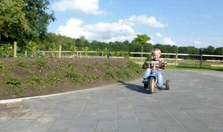 Kind auf Dreirad in der Auffahrt