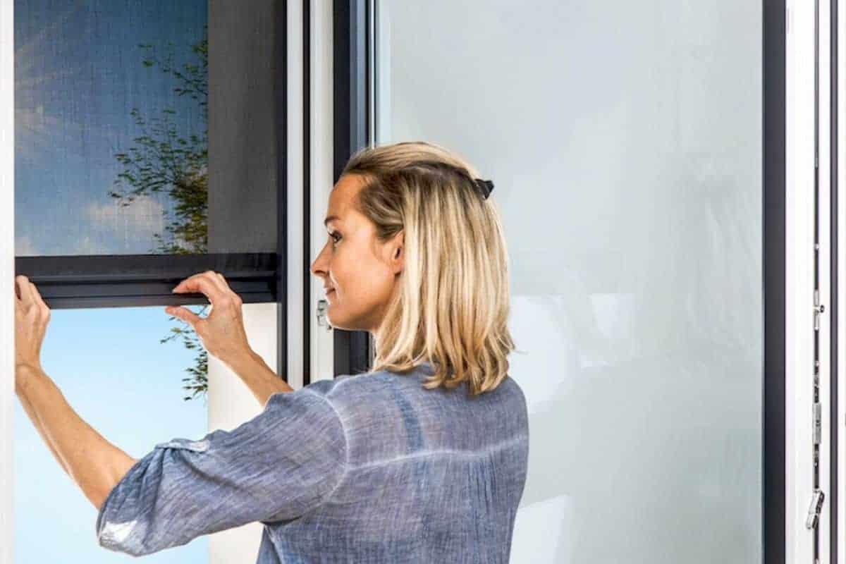 Frau zieht Rollo am Fenster
