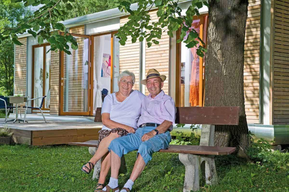 Ehepaar sitzt auf Bank vor Zuhause