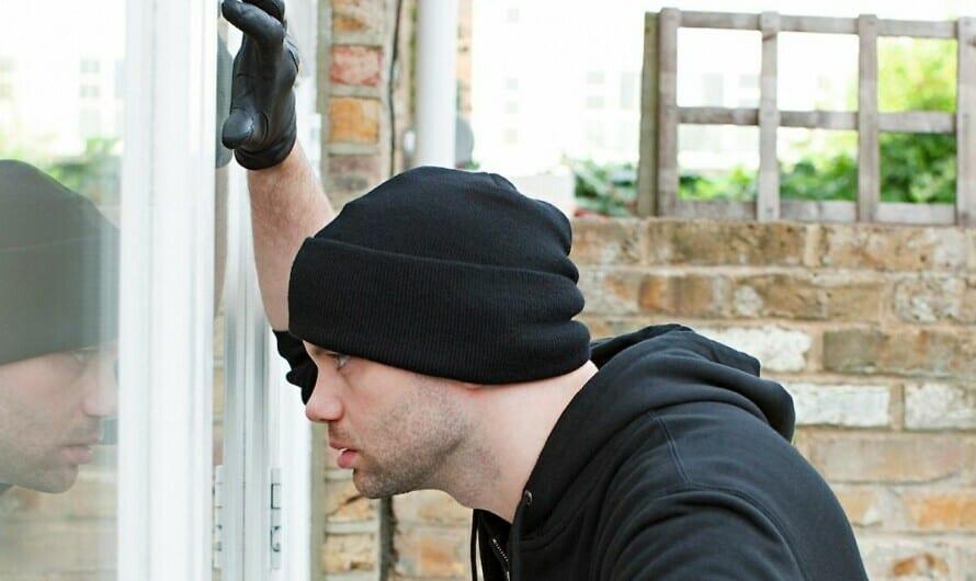 Einbrecher steht vor Fenster