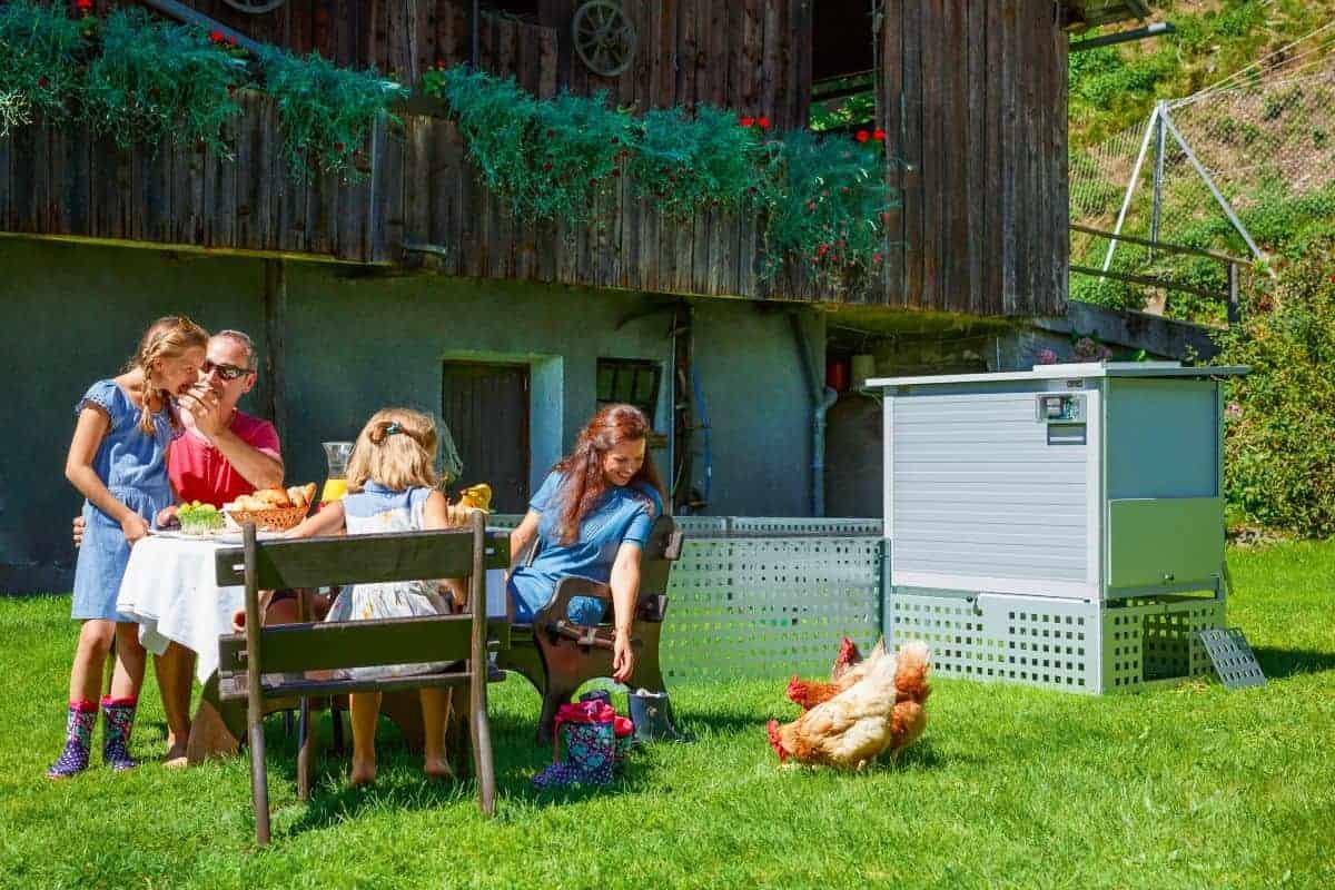 Familie am Gartentisch mit Hühnern