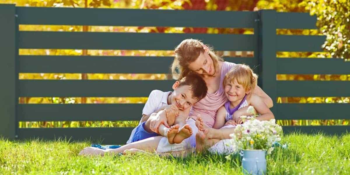 Mutter mit Kindern vor Zaun