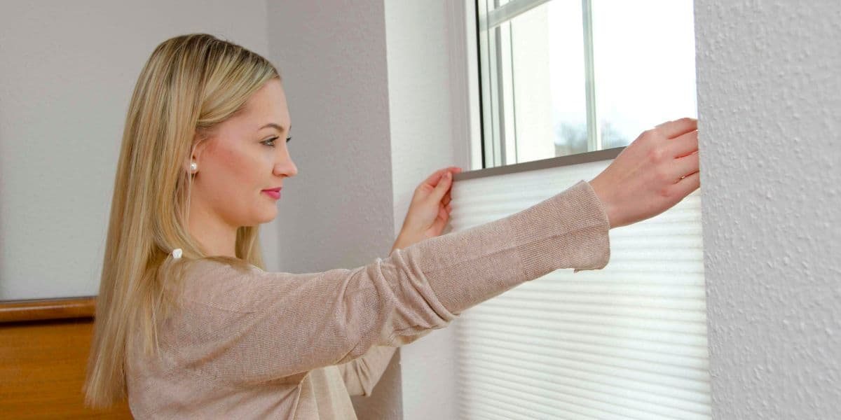Frau öffnet Plissees am Fenster