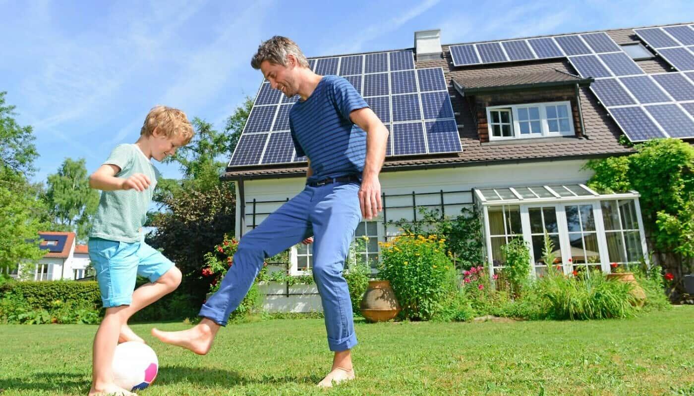 Vater mit Sohn vor Haus mit Solaranlage