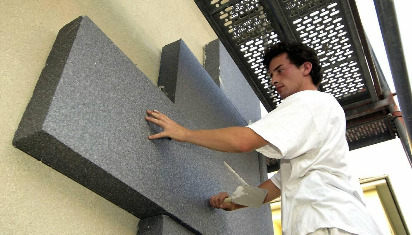 Bauarbeiter dämmt Fassade