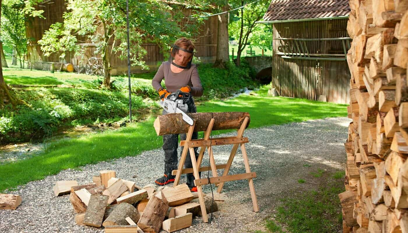 Frau beim Brennholz sägen